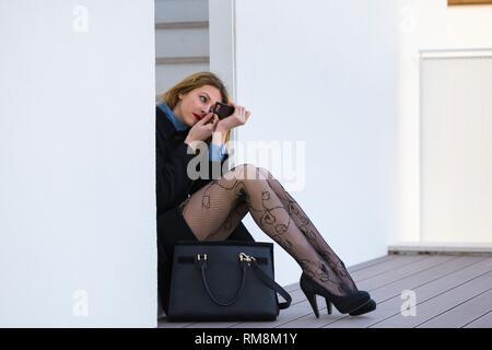 Pretty teenager girl legs heels fixing make-up spontaneous - Stock Image