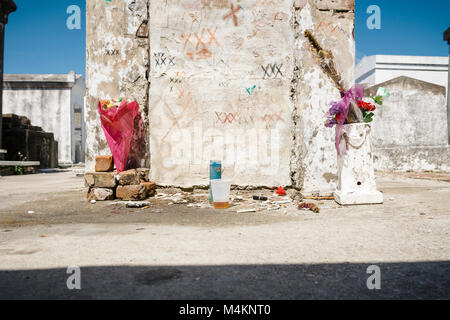 A tomb in the historic St Louis Cemetery No. 1, New Orleans, Louisiana, USA, with grave offerings and graffiti associated - Stock Image