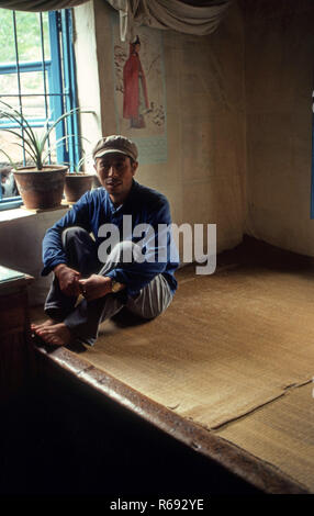Northern China 1980 Commune in Waoning Province in an interior of a home where a man is sitting on a kang a bed stove which is a platform made of brick where funnelled air is fuelled by a fire providing heat, usually wood fire. - Stock Image