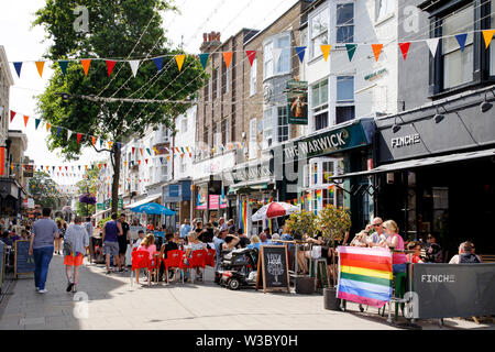 WORTHING, UK - JULY 13, 2019: People enjoying day out in the town decorated for Gay Pride Parade - Stock Image