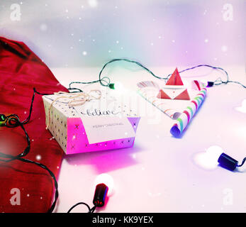 Christmas Decoration with Gifts and Lights with candy cane and golden color bokeh with purple color process for - Stock Image