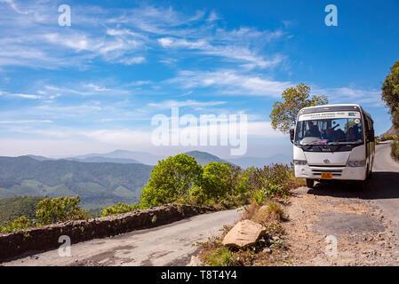 Horizontal view of a coach transporting people around Eravikulam National Park in Munnar, India. - Stock Image
