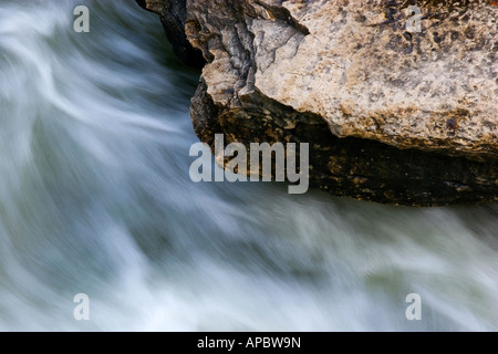 Water rushes past an outcropping below the water fall at the Tanyard Creek Trail in Bella Vista, Ark. - Stock Image