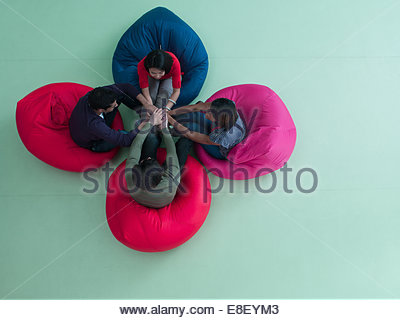 Smiling business people sitting in bean bag chairs with stacked hands - Stock Image
