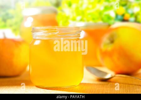 Homemade apple jelly in glass jars with fresh apples and a spoon on a wooden table in front of trees in bright sunshine - Stock Image