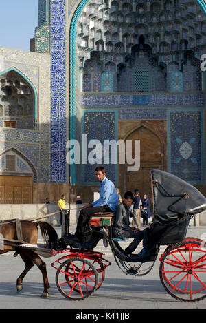 Horse drawn cart carrying Iranian domestic tourists, Imam Square, Isfahan, Iran - Stock Image