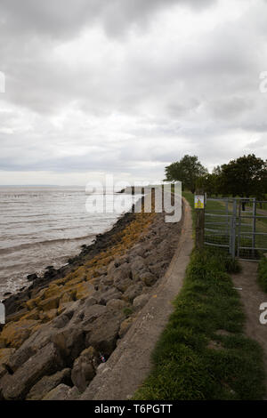 Goldcliff, Newport, UK. 2nd May, 2019. People walk along the sea wall despite a Windy, Grey and Dismal day in Goldcliff, Newport, Wales. The sea wall overlooks the River Severn giving amazing views across the water. Credit: Keith Larby/Alamy Live News - Stock Image