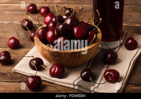 Cherry in bowl with juice on a wooden background - Stock Image