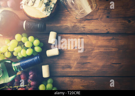 wine bottles grapes and cheese on wooden background. top view copyspace - Stock Image