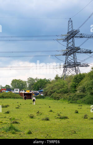 View across a field of a large electricity pylon, power lines and car scrapyard in Nursling, Test Valley, Southampton, Hampshire, southern England, UK - Stock Image