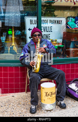 ASHEVILLE, NC, USA-2/16/19: A saxophonist sitting on folding chair and busking. - Stock Image