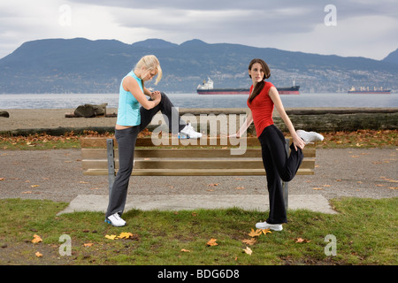 Two young women stretching their muscles at Spanish Bank Beach in Vancouver, British Columbia, Canada - Stock Image
