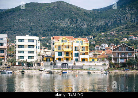 Beautiful view on the background of the mountains on residential buildings or the architecture of the coastal city of Tivat in Montenegro. - Stock Image