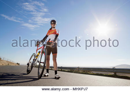 Female cyclist with race bicycle on sunny open road - Stock Image