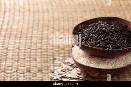 Black wild rice and basmati rice in bowls on a straw background - Stock Image