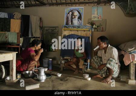 BANGLADESH Family of Garo tribal minority eating breakfast inside their house, Haluaghat, Mymensingh region photo by Sean Sprague - Stock Image