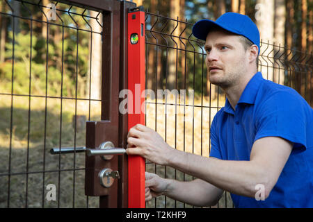 fence construction - worker check the level of metal post - Stock Image
