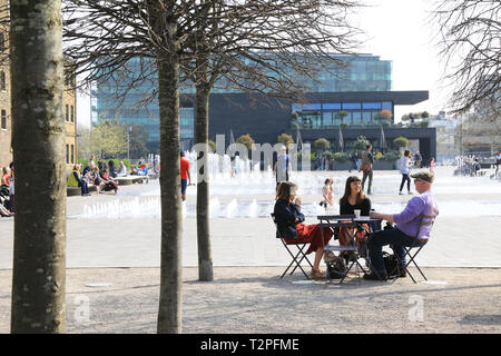 Relaxing by the fountains in spring sunshine on Granary Square, at Kings Cross, north London, UK - Stock Image