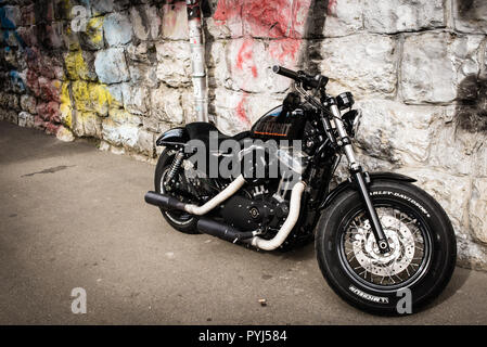 Zurich, Switzerland - March 2017: Black motorcycle 2017 Sportster Forty-Eight, motorbike Harley-Davidson with stone wall and graffiti in background - Stock Image