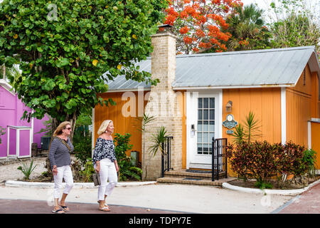 Captiva Island Florida 'Tween Waters Inn Island Resort & Spa hotel guest cottage exterior chimney tropical foliage woman strolling friends - Stock Image