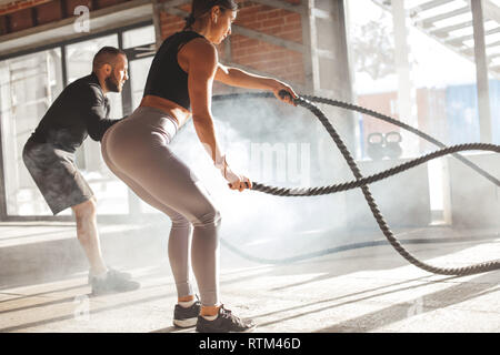 Caucasian fit couple exercising with battle ropes at gym. Woman and man dressed in sports outfit training together doing battling rope workout, with p - Stock Image