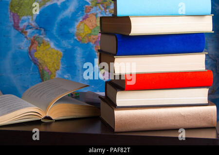 Composition of books and studies on table with world map hanging on wall - Stock Image