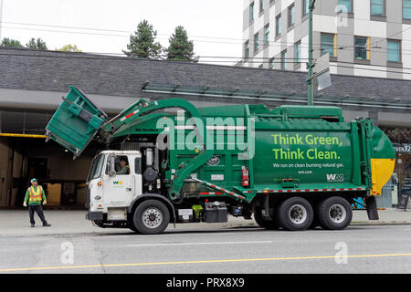 Green clean energy waste management garbage truck lifting a dumpster, Vancouver, BC, Canada - Stock Image