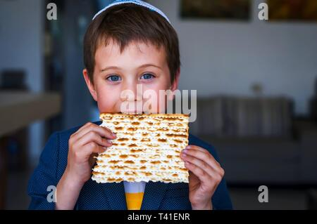 Cute Caucasian Jewish boy holding in his hands and taking a bite from a traditional Jewish matzo unleavened bread. Jewish Passover Pesach concept - Stock Image