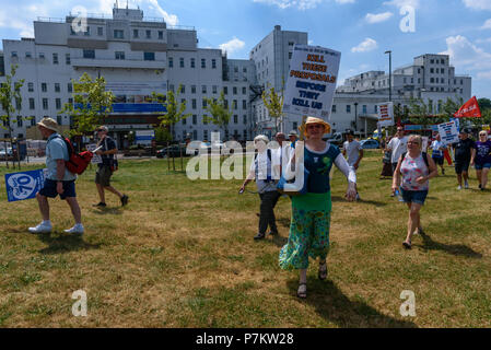 London, UK. 7th July 2018. Keep Our St Helier Hospital (KOSHH) campaigners against the closure of acute facilities at Epsom and St Helier Hospitals in south London celebrating the 70th Birthday of the NHS with a march from Sutton arrive in front of St Helier Hospital for a rally.  The closures are prompted by government cuts which call for huge savings by the trust, and would leave a wide swa Credit: Peter Marshall/Alamy Live News - Stock Image