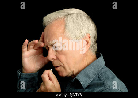 A grey haired man in his sixties taking a tablet - Stock Image
