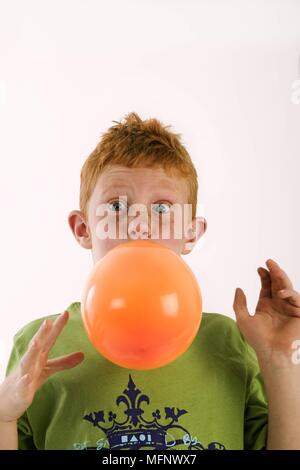 Young boy with red hair and freckles age 7, blowing up an orange balloon. Model released. Studio shot.       Ref: CRB538_103609_0044  COMPULSORY CREDI - Stock Image