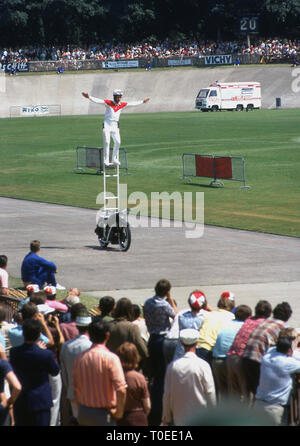 1974, tricks motorcyclist standing on a ladder riding a motorcycle entertaining the spectators at the finish of the Tour de France cycle race on the track at the Velodrome de Vincennes, Paris, France. This was the last year the Tour finished at the velodrome as the following year it moved to the Champs-Elysees. - Stock Image