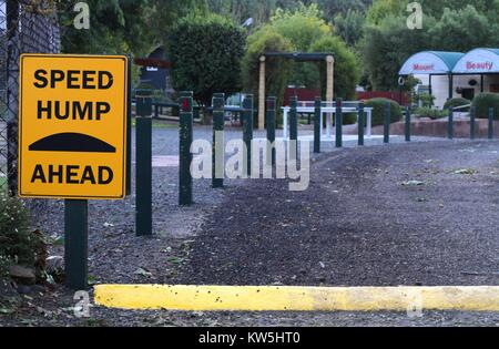 Speed hump sign beside a driveway with fence behind. - Stock Image