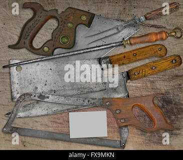 vintage butcher shop tools over stained wooden table,space on business card for your text - Stock Image