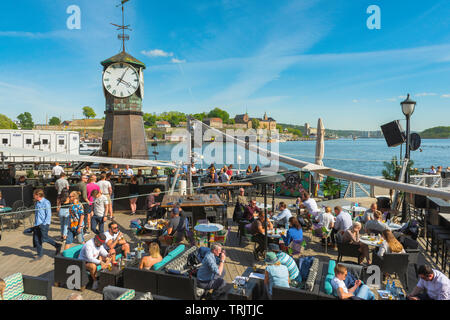 Oslo Aker Brygge, view of people relaxing on a summer afternoon on a terrace bar along the Stranden in the Aker Brygge harbour area of Oslo. - Stock Image