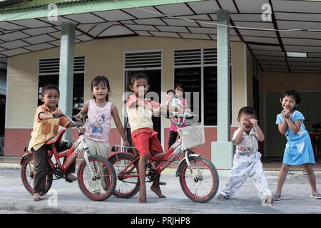 Happy children posing for a photo at Afulu village on Nias Island, north Sumatra, Indonesia - Stock Image