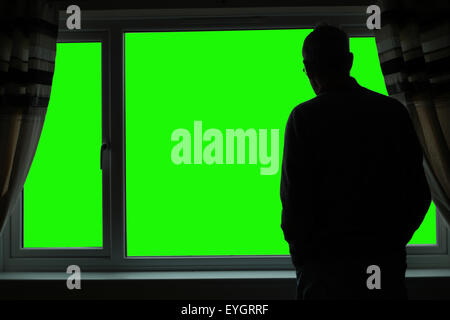 Chroma-key silhouette of a senior man back to camera, looking out of a window. Space for your own background. - Stock Image