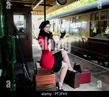 Vintage beautiful female wearing red dress and black beret, sitting on suitcases, looking in mirror and applying her lipstick. - Stock Image
