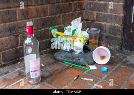 Litter including packaging from fast food outlets and an empty glass wine bottle dumped in a shop doorway in Windsor, UK - Stock Image
