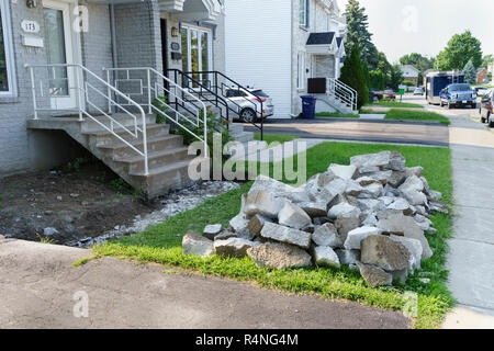 Pile of concrete debris left after the demolition of an alley leading to the front entrance of a suburban house. - Stock Image