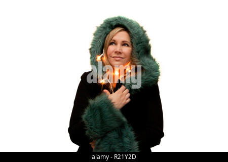 Model in festive green furry coat and holiday lights looking up happily thinking of the holidays - Stock Image