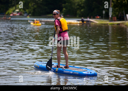 A single female paddle boarding on a lake in Bella Vista, Arkansas, USA. - Stock Image