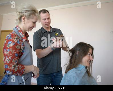 International Space Station Expedition 59 crew member Christina Koch of NASA has her hair cut by a stylist as fellow crew member, Nick Hague of NASA, assists at the Baikonur Cosmodrome March 12, 2019 in Baikonur, Kazakhstan. Expedition 59 crew: Christina Koch of NASA, Alexey Ovchinin of Roscosmos, and Nick Hague of NASA will launch March 14th onboard the Soyuz MS-12 spacecraft for a six-and-a-half month mission on the International Space Station. - Stock Image