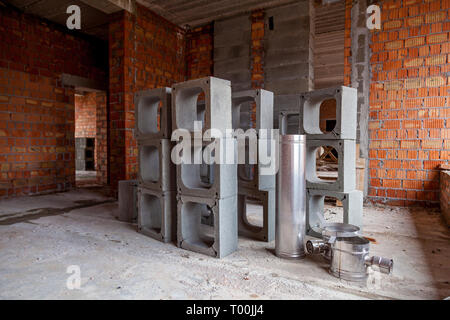 Walls of a multi-storey red brick house. Construction site, tools, wheel barrow, sand and bricks at new house building, cement mixer machine and acces - Stock Image
