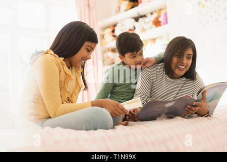 Mother reading book to children on bed - Stock Image