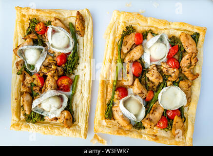 Summer food: meal served outdoors with goat's cheese, broccoli, tomatoes and chicken on puff pastry slices - Stock Image