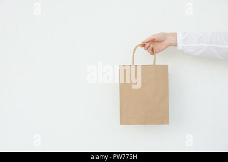 Young caucasian woman holds in hand empty blank mock up brown craft paper bag on white wall background. Christmas New Years present shopping sale. Con - Stock Image