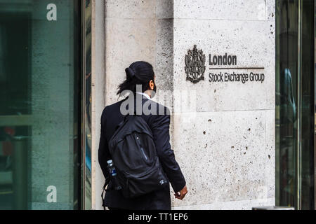 London Stock Exchange - a City worker passes the London Stock Exchange building at 10 Paternoster Row in the City of London Financial District - Stock Image
