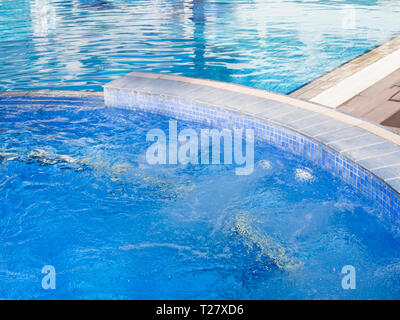 A clean azure blue swimming pool with heated water and access to bubbling massage jets is a holiday dream for many who travel to Cyprus in the autumn - Stock Image