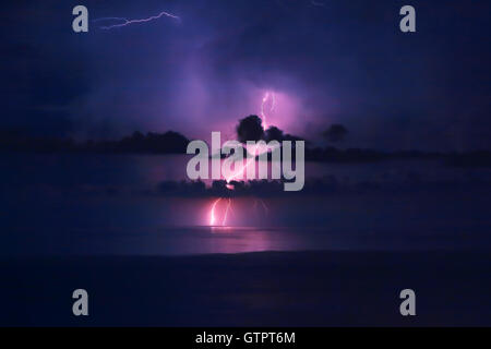 Beautiful dramatic landscape, bright pink lightning over water, storm in the sea, autumn weather, amazing natural - Stock Image